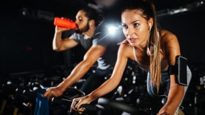 woman doing cardio while riding a bicycle at the gym.
